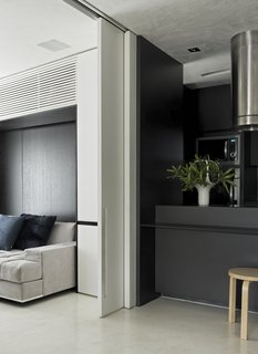A Brazilian Bachelor Pad Embraces Light and Darkness - Photo 7 of 8 - A sliding door to the guest bedroom makes this flexible area even more accessible. A burnt cement floor connects this room to the kitchen.