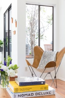 The butterfly chair in the living room was sourced from Urban Outfitters, and books rest on Article nesting tables.