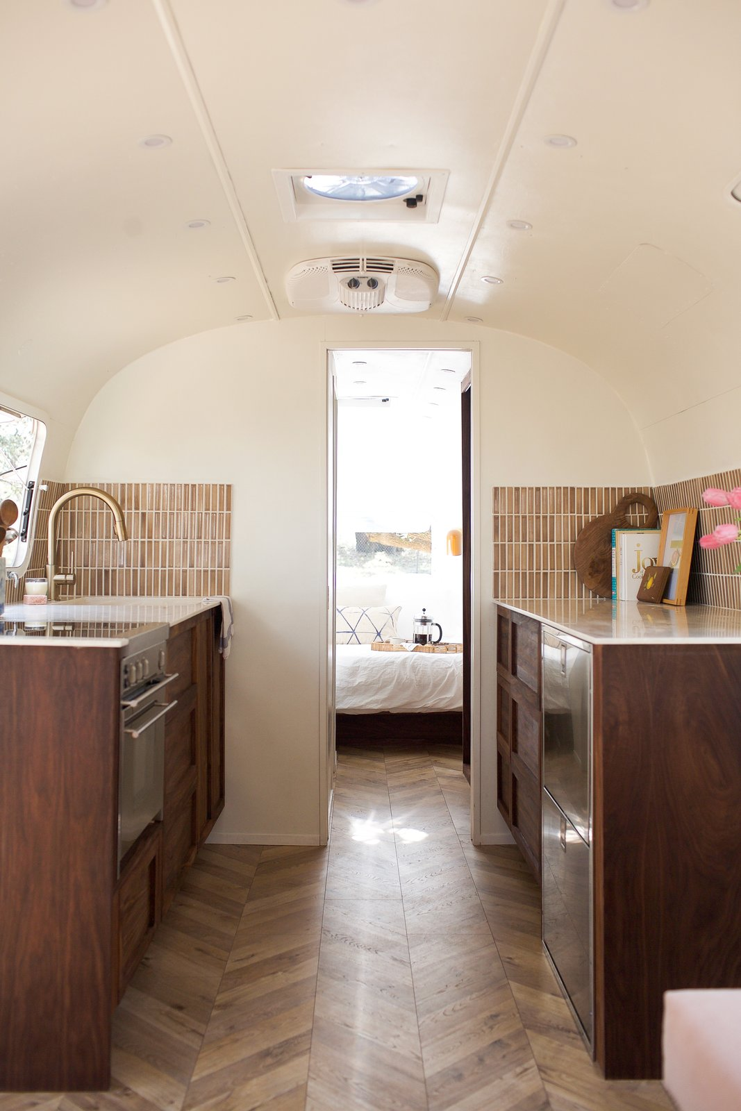 Kitchen, Marble, Ceramic Tile, Wood, Medium Hardwood, Refrigerator, Cooktops, Drop In, Wall Oven, and Recessed  Best Kitchen Cooktops Drop In Wall Oven Marble Photos from This Chic Camper Will Make You Want to Be an Airstream Dweller