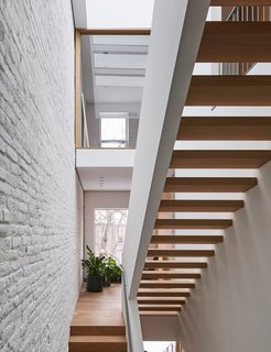 """There aren't many row houses that treat vertical circulation and the relationship between public and private spaces the same way as [this house],"" Shane says. White oak treads and a painted steel handrail make up the home's signature staircase."