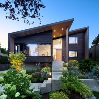 """""""Exterior materials include black anodized-aluminum windows, stained western red cedar, and pre-painted metal siding,"""" Parish says. """"These materials complement the new modern volume of the house, while also nodding to the existing character of the neighborhood."""""""