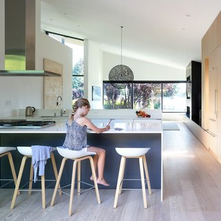 Hay stools are lined in the completely renovated kitchen, which is punctuated by an abundance of natural light and a large Moooi Random Light.