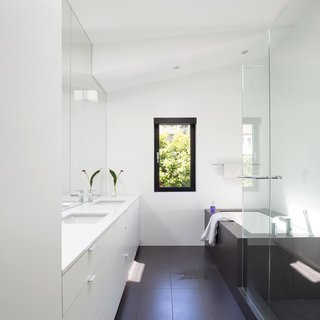 Porcelain floor tiles and Caesarstone countertops encompass the master bathroom, which also includes a pair of Duravit sinks and Aquabrass faucets.