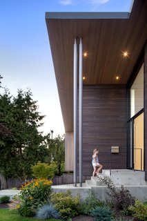 The exterior's many textures include stained western red cedar siding, a white oak veneer front door, and a concrete walkway.