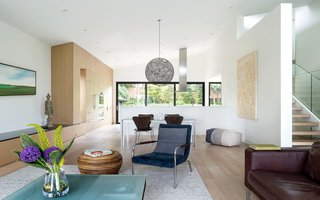 """The newly opened kitchen, dining, and living space connect the home from front to back,"""" Parish adds. """"Operable windows on both ends allow for cross ventilation and unobstructed views, too."""" White oak millwork is shown throughout the space, including on the appliances."""
