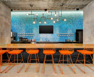 Techspace Austin's vibrant kitchen area features a custom bar designed by DoveTail Custom Woodworks.