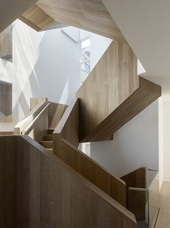 In a major renovation of a San Francisco townhouse, a striking interior stair crafted of fumed and stained oak panels that clad an asymmetrical sculptural stair. The incorporation of a light well at the top of the stair floods it with light.
