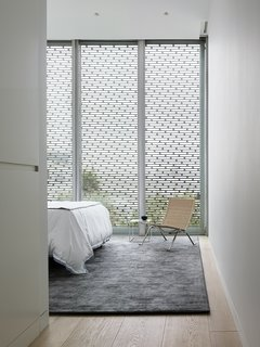The master bedroom, modest in size, features a Stark area rug and a wicker PK22 chair by Poul Kjærholm for Fritz Hansen.