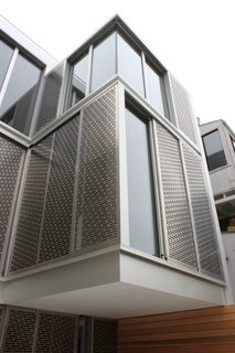 The home's dramatic rear facade is composed of perforated metal screens by Flynn & Enslow, which are attached to Fleetwood windows. The second-floor bump out is cantilevered with no structural post below.