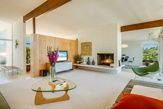 Original to the home, the large double-sided fireplace anchors the main floor's living room.