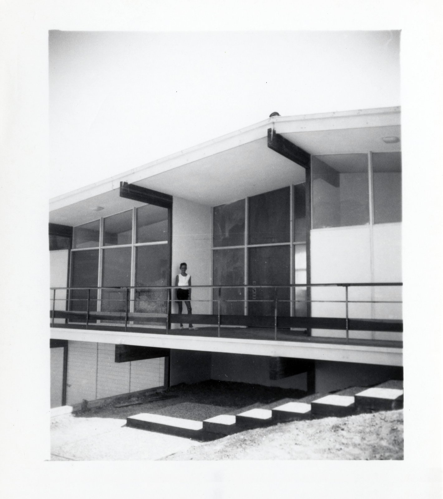 DeLeeuw Residence black and white historic photo of mid century home exterior with person standing on upper level patio.