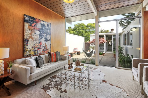 The living room has original wood paneling and floor-to-ceiling windows with courtyard access.