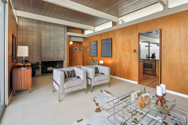 The original wood-burning, cinder-block fireplace remains intact, while clerestory windows allow light to pass between the kitchen and living room.