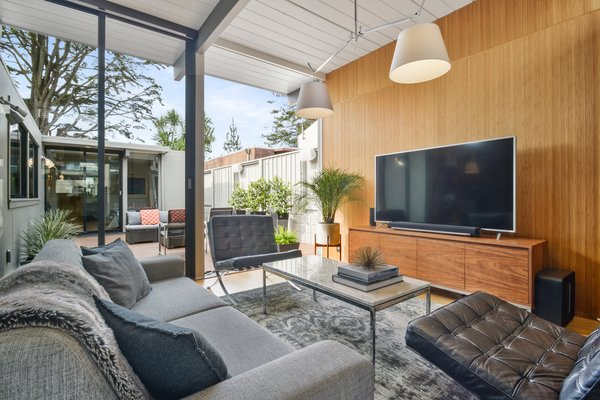 The inviting living room's floor-to-ceiling windows and glass doors open up to the courtyard for breezy indoor/outdoor living.