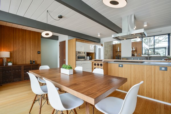 Warm wood tones dominate the open kitchen and dining area, with custom cabinetry by Redtail Woodworks.