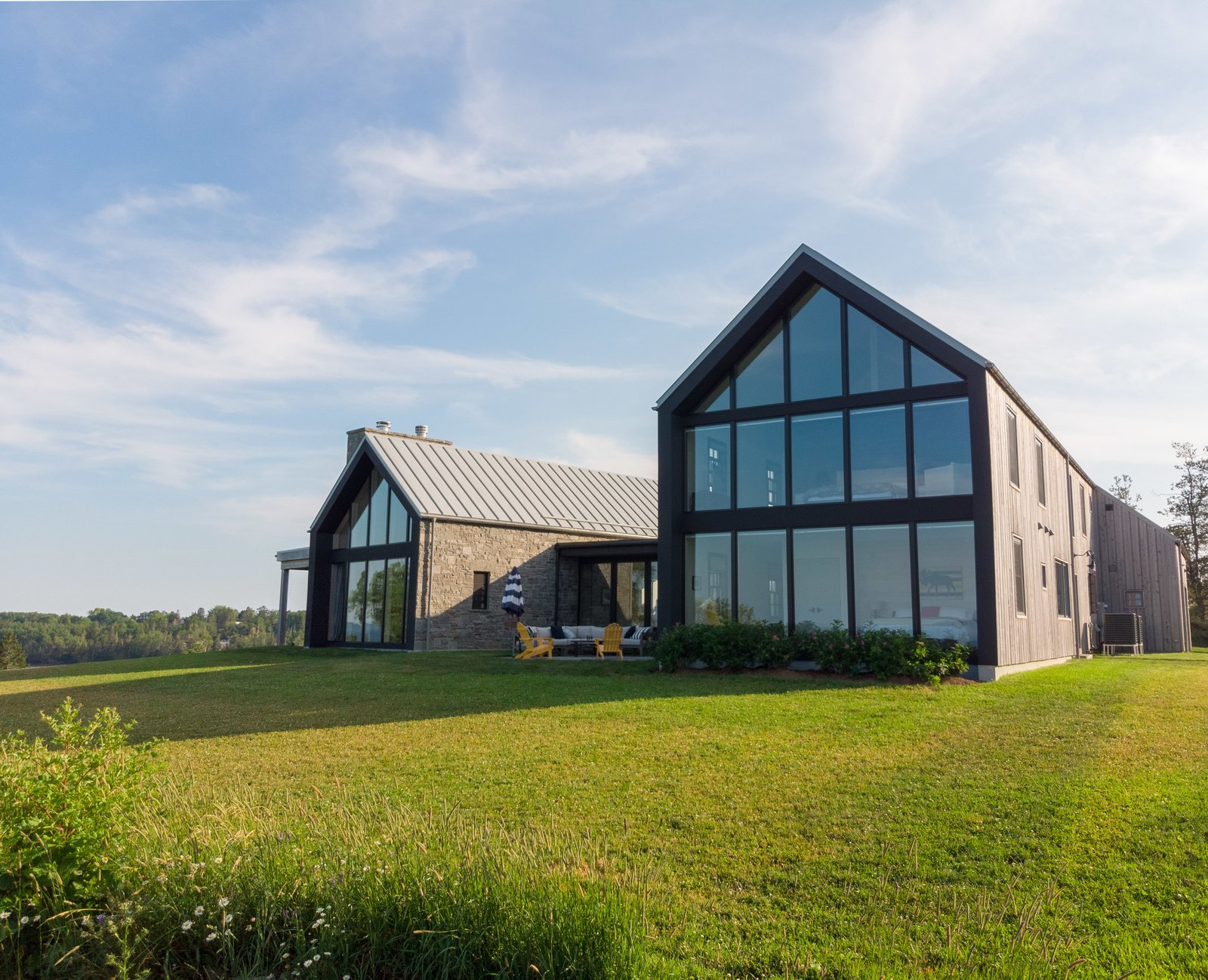 Exterior, Farmhouse Building Type, House Building Type, Metal Roof Material, Stone Siding Material, Wood Siding Material, Glass Siding Material, and Gable RoofLine  Best Photos from One Couple's Contemporary Coastal Retreat Celebrates Their Irish Roots