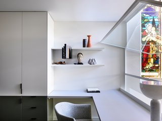 Introducing low-profile, white-frame windows at spaces bordering the void allows interior rooms to benefit from added light and air circulation.