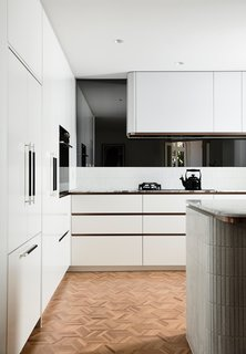The light and airy kitchen features a gently curved hood and island, which echo the design play throughout the house. Appliances by Fisher & Paykel are hidden behind custom fronts for a clean and streamlined aesthetic in the compact space.