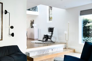 """The home's living room, adjacent to the three-story """"void,"""" enjoys plentiful natural light. A Beaubien Wall Double Shade sconce by Lambert & Fils and Arancini Floor Lamp by Moda Piera accent the space."""
