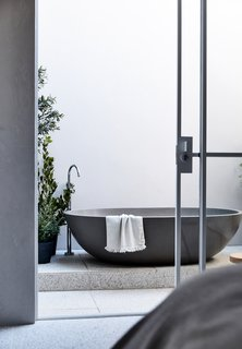 An outdoor bathing area adjoining the master bedroom was a unique request from the clients. Stone soaking tub and terrazzo pavers complete the inviting retreat.