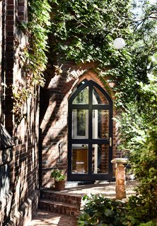 """Doherty Design Studio embraced original character details of the church, including the beautiful, arched glass doorway to the tower. When homeowner Jennifer and Grant initially viewed the space, the stunning tower """"was just the icing on the cake."""""""