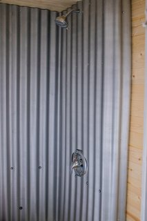 """The new bathroom includes a polycarbonate shower, which has been spray-painted silver to mimic corrugated iron. """"We chose polycarbonate because it's lightweight, more malleable, and a cheaper option than actually using metal,"""" adds Grace."""