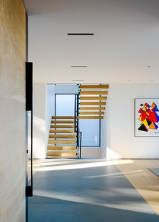 Intimately tied to the steep topography, views and experiences change as one travels through the home. Traveling up the steep entry to the living level on the second floor, the entry space offers access to both the living room to the north, and private dining and kitchen area to the south. Wide-plank European white oak flooring, and Pietra Serena limestone slab inlays bring an organic warmth to the space.