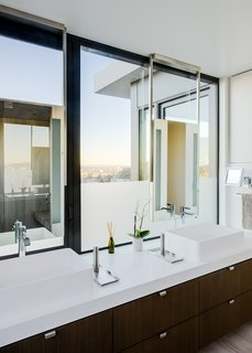The bright master bedroom, with vessel sinks and Caesarstone counters, also enjoys sweeping city views.