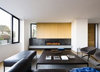 In the living room, rift cut white oak millwork marries wax steel detailing at the striking fireplace.