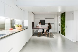 A vibrant living wall brings nature and organic warmth into the space. An idea first proposed by the owners, the vertical garden was further designed and developed by Cónica Studio.