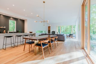 The open kitchen and living room features a handcrafted walnut dining table designed by Marica, which sits beneath a brass chandelier she designed and built herself.