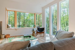 A cozy white oak window bench sits beneath an impressive Marvin Contemporary Corner Window, overlooking beautiful southwest vistas. This southern vantage point, and the window nook in particular, was a cornerstone of the home's design and orientation.