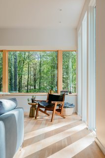The south-facing facade, where the sun sets in the evening, is the couple's favorite spot on the property. Creating expansive openings with this exposure allowed an intimate and inspiring connection with the wooded landscape.