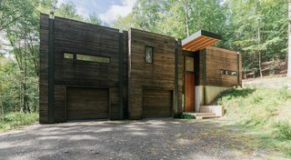 """Positioned on a sloping hillside, the home is built into the land. The lower level is reserved for Marica and Brock's """"play"""" space, a workshop and garage, while the upper level houses the bright and airy living quarters."""