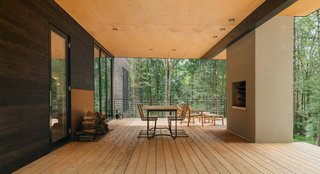 It was important to the couple that the home's deck be an extension of the living level, neither above nor below it. Sitting on ground level, the spacious deck offers fluid access to the surrounding wooded landscapes, while simultaneously inviting nature in.
