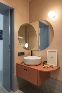 The coral-hued bathroom features a custom vanity designed by CaSA, a Green 42 vessel sink by Catalano, a LEAF faucet by Bruma, and grey ceramic floor tile by Ceramica Vogue.