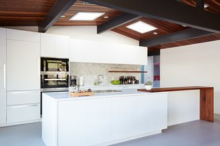 The relocated kitchen is anchored to one side of the home, rendering the rest of the space open and usable. White custom cabinetry and Caesarstone counters keep the room bright and airy. The kitchen appliances are from Miele, with the addition of a Sub-Zero refrigerator and ceiling-mounted Futuro Futuro flush range hood.