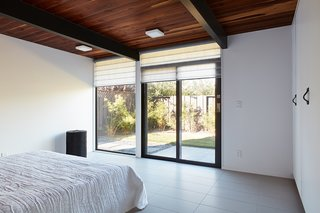 The spacious master bedroom enjoys plentiful light and direct access to the backyard.