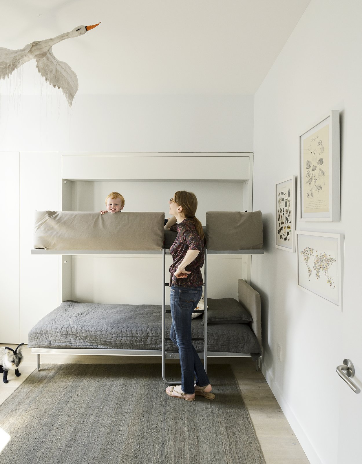 Kids Room, Bedroom Room Type, Bunks, Light Hardwood Floor, and Rug Floor  Photo 1 of 8 in 7 Ways to Child-Proof Your Home Without Forgoing Style from Making Room for Baby  (And You)