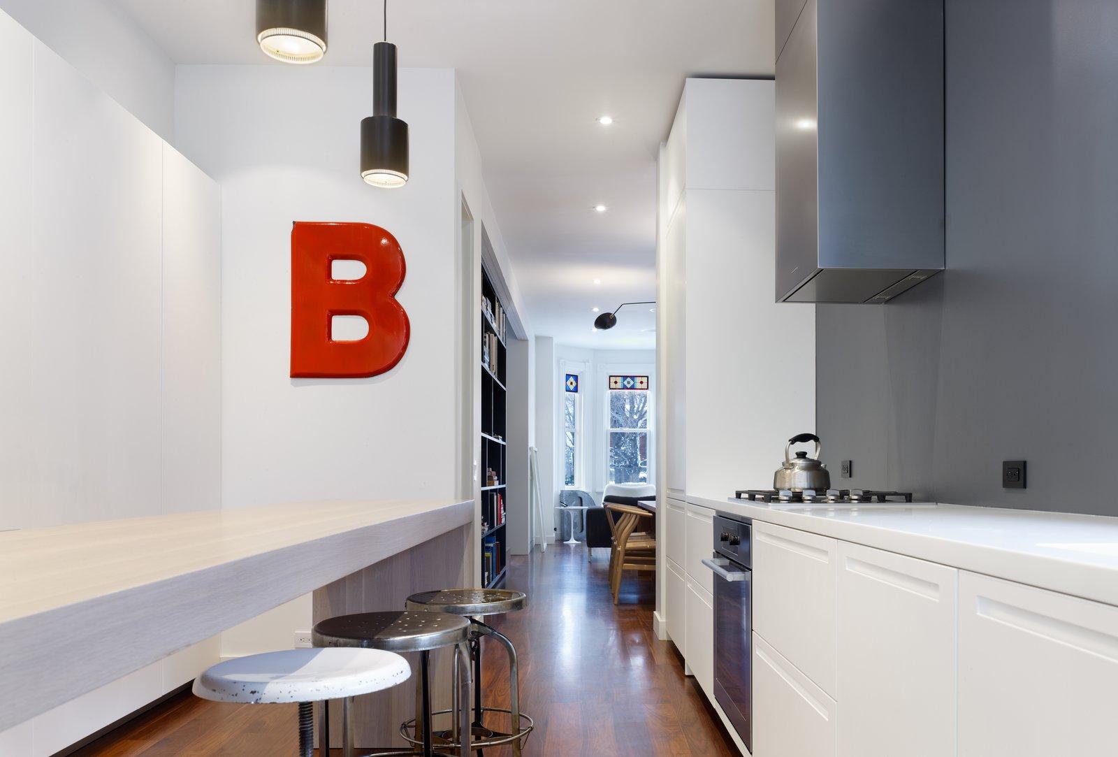 Kitchen, Recessed Lighting, White Cabinet, Range Hood, Cooktops, Range, Pendant Lighting, and Medium Hardwood Floor  Contrast House