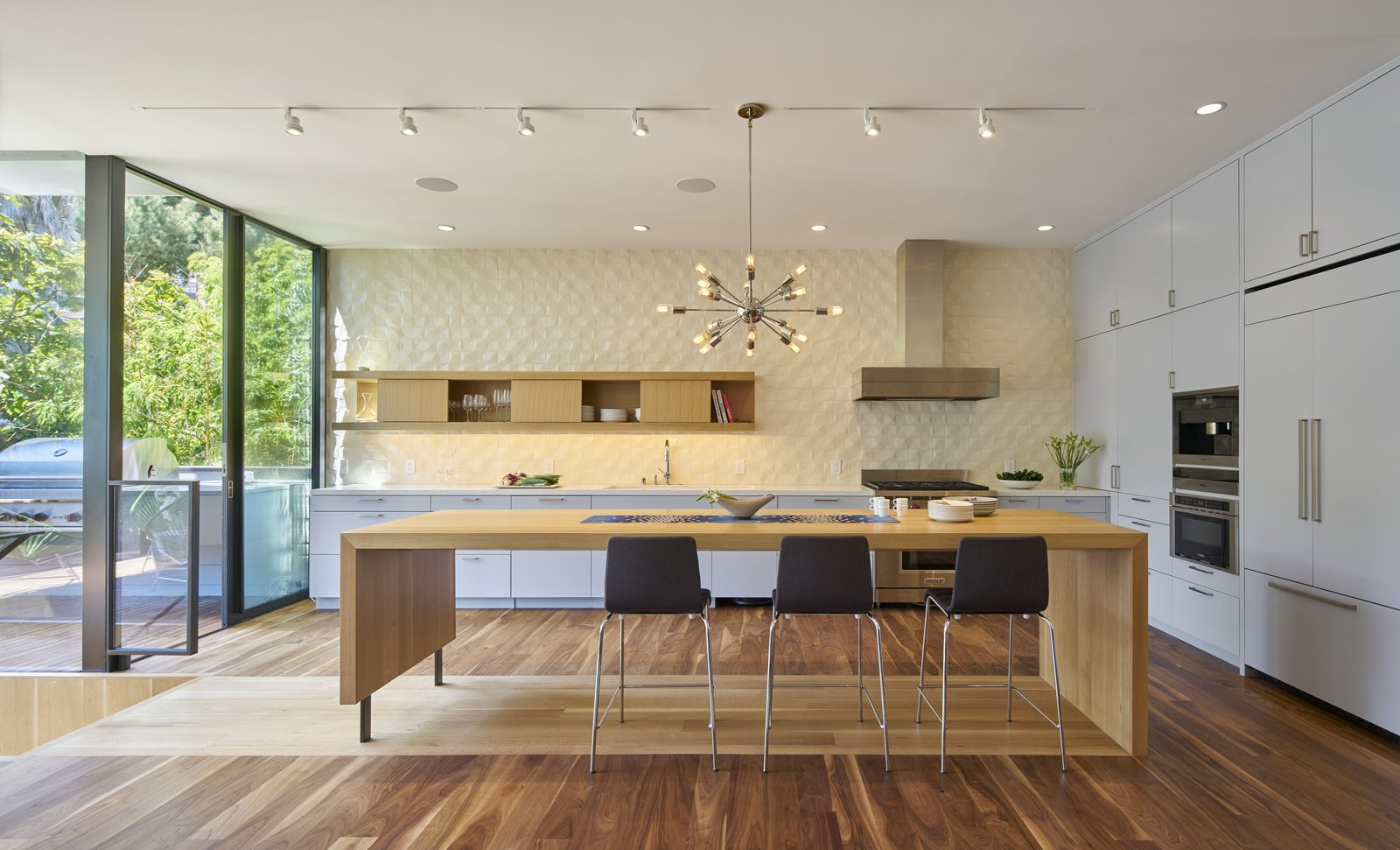 Kitchen, Dark Hardwood Floor, Colorful Cabinet, Wood Cabinet, Light Hardwood Floor, Pendant Lighting, Track Lighting, Refrigerator, Wall Oven, Microwave, Range, and Range Hood  29th Street Residence by Schwartz and Architecture
