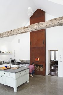 A Cor-Ten steel panel tower that's been acid-oxodized and weathered over three years houses a wood-burning pizza oven at its base.