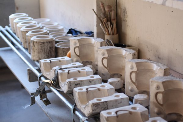 """More complicated and hollow forms are made by slipcasting. Liquid clay (called slip) is poured into plaster molds (that we make on-site). The clay dries for 20-30 minutes, the remainder of the liquid clay is poured out and a """"wall"""" of clay that has already dried remains. Considerable work is still needed to finish the piece as the mold leaves lines of clay """"flash"""" on the piece, and a lot of skill is required to make it look as the design was intended to look."""