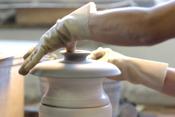 Many details require an addition step. Here, a lid is pulled off the wet clay when it is being formed. This handle is for a casserole lid. There is no mold for this piece, so each finished lid has its own character.