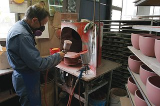Glaze is applied to the pieces by hand with a spray gun.