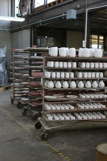 Formed, trimmed and glazed pieces wait to be fired on a ware cart.