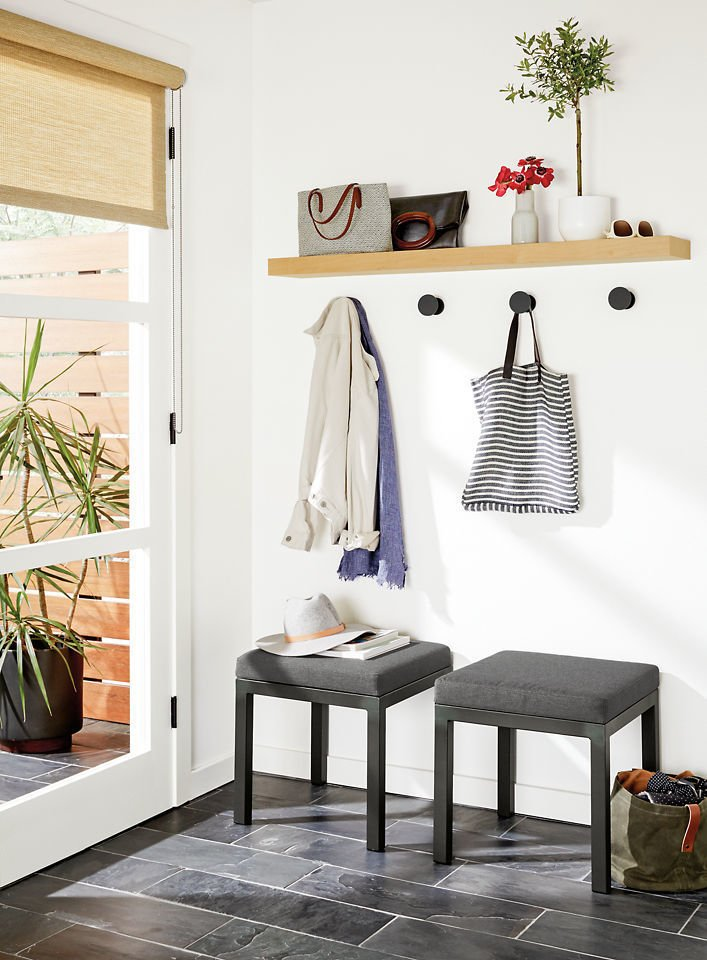 A drop-off station can consist of anything, from nothing more than a narrow shelf with a mirror above it, to a series of hooks with seating, storage, and plants.