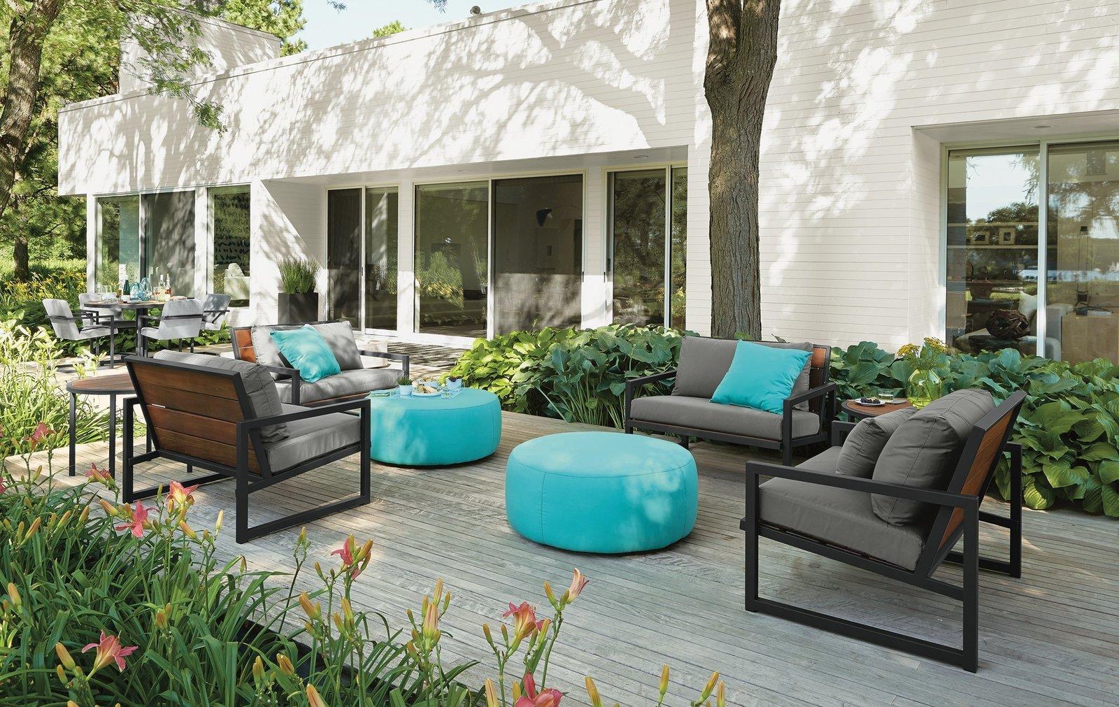 Outdoor, Back Yard, Large Patio, Porch, Deck, Wood Patio, Porch, Deck, Gardens, and Shrubs Montego sofa with cushions, Montego lounge chair with cushions, Boyd round ottoman, solid outdoor pillows  Photo 8 of 8 in Expert Design Advice: Outdoor Dining Spaces