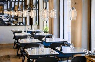 Guests Enjoy Meal Under Modern Restaurant Pendant Lighting in Sweden