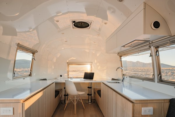 The kitchen and convertible desk area of the Kugelschiff display a luminous, white-painted ceiling and walls, and white ash cabinetry and flooring.